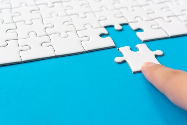 Hand die stuk van witte puzzel op blauwe achtergrond zet