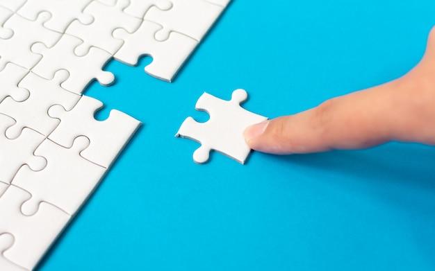 Hand die stuk van witte puzzel op blauwe achtergrond zet.