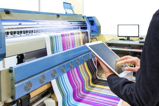 Hand die tabletbediening gebruikt met inkjetprinter die veelkleurig vinyl afdrukt