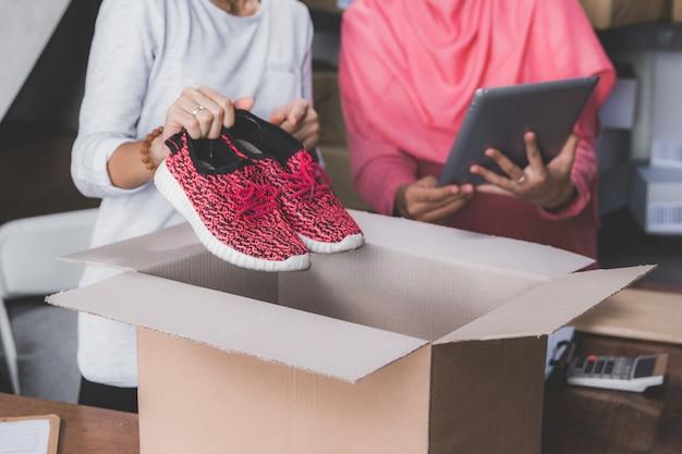 Hand die te verschepen schoenen voorbereidt