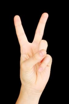 Hand die teken maakt dat op zwarte muur wordt geïsoleerd