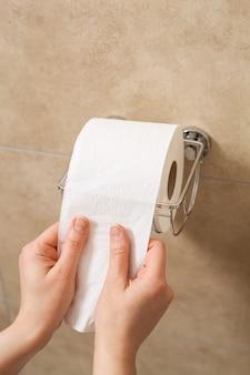 Hand die toiletpapierrol in houder trekt