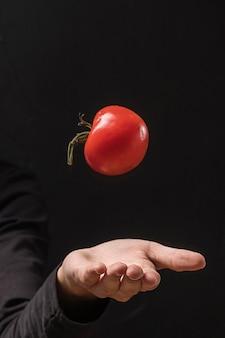 Hand die tomaat overgeven in de lucht