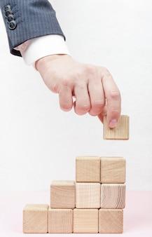 Hand die treden maakt van houten kubussen