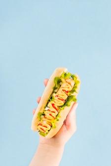 Hand die van de close-up de hoogste mening hotdog houdt