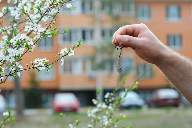 Hand die van makelaar sleutel houdt aan een droomhuis