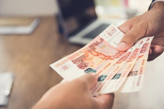 Hand die van zakenman geld, russische roebel (rub) munt geeft, aan zijn partner
