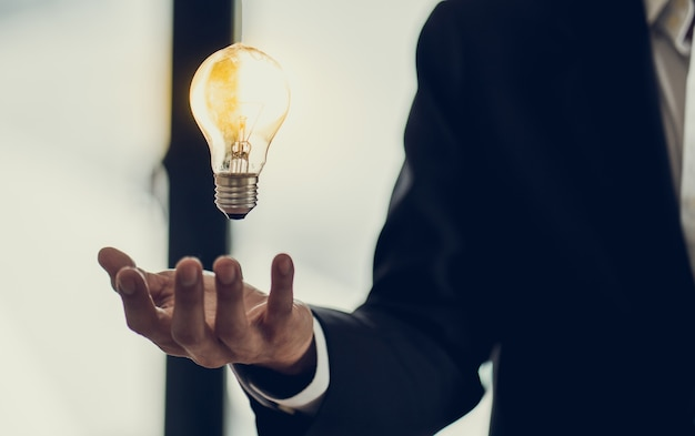 Hand die van zakenman gloeilamp houdt als symbool van succesidee, het concept van de innovatieinspiratie