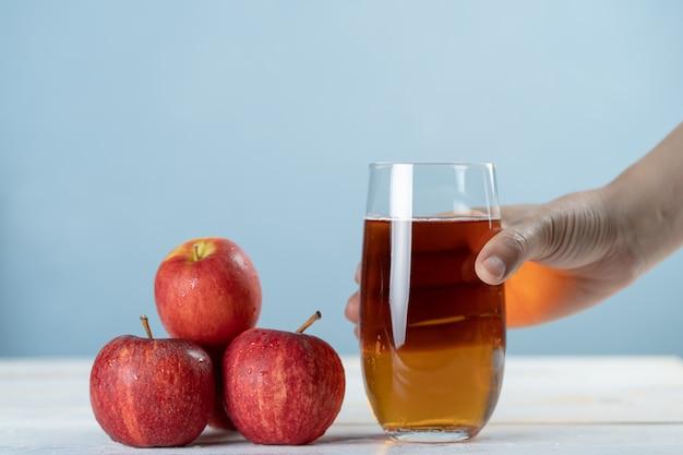 Hand die vers appelsap in het glas houdt