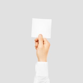 Hand die vierkante lege witte kaart geïsoleerd houdt