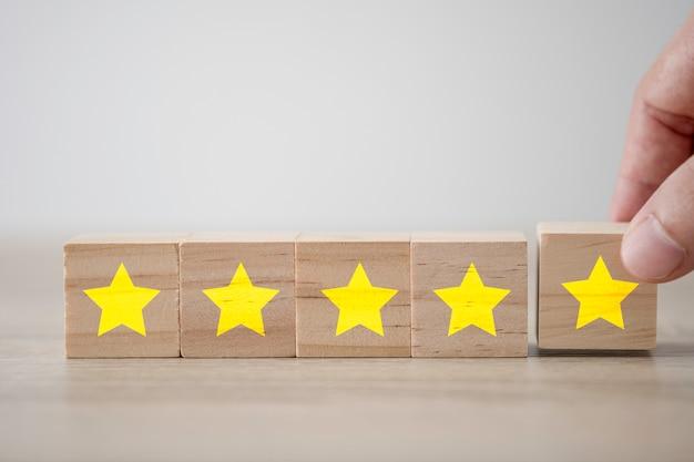 Hand die vijf gele sterren zet die het scherm op houten kubus drukken. klantervaringsonderzoek en tevredenheidsfeedbackconcept.