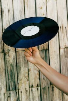 Hand die vinylverslag over houten achtergrond houdt