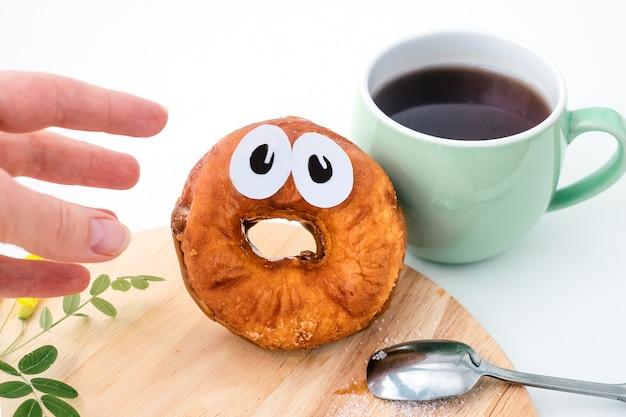 Hand die voor doen schrikken doughnut met document ogen bereikt