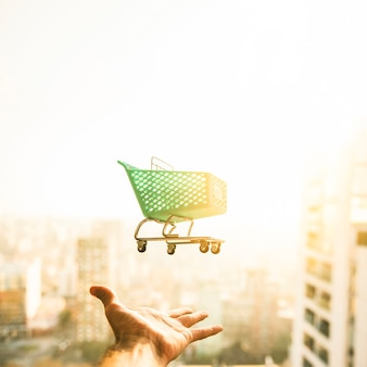 Hand die voor kruidenierswinkelkar op vage achtergrond bereikt
