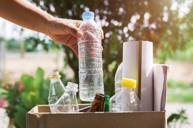 Hand die vuilnisflesplastiek houden die in kringloopzak voor het schoonmaken zetten