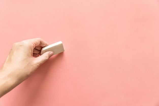 Hand die wit rubber voor het wissen van iets op lege roze achtergrond houdt. abstracte achtergrond met kopie ruimte.