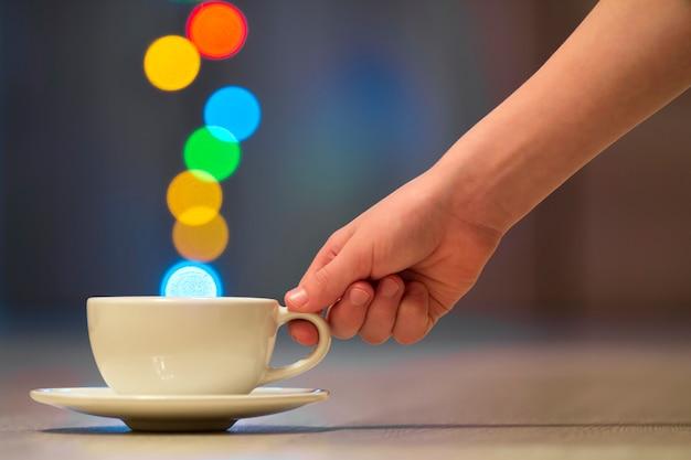 Hand die witte kop van koffie met kleurrijke bokehstoom houdt