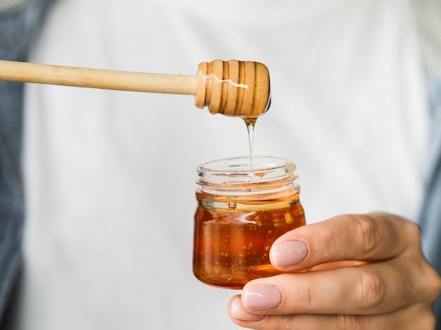 Hand die zoete honingskruik houdt