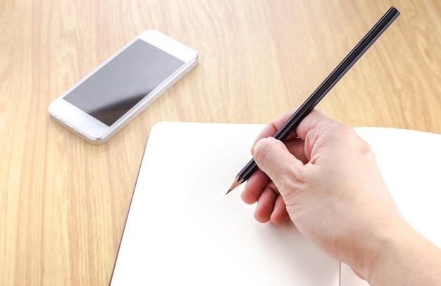 Hand die zwart potlood houdt en op leeg open notitieboekje met smartphone naast het op houten lijst schrijft