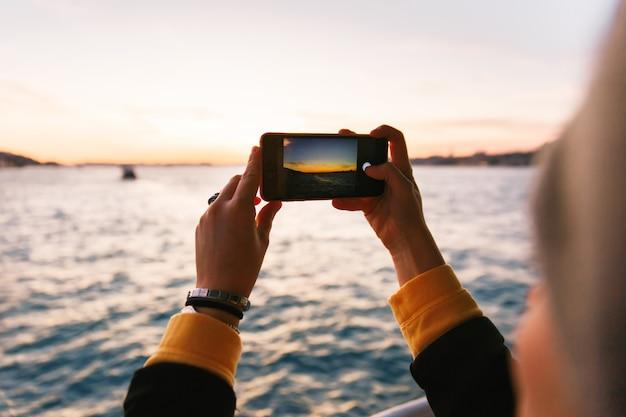 Hand die zwarte smartphone houden die een foto van bosphorus-straat nemen bij zonsonderganglicht
