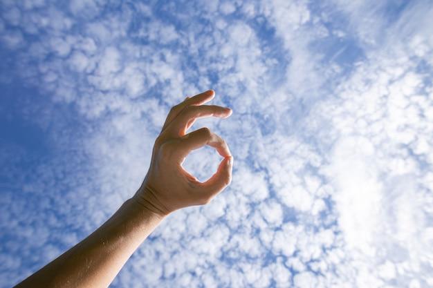 Hand doet goed teken tegen hemel