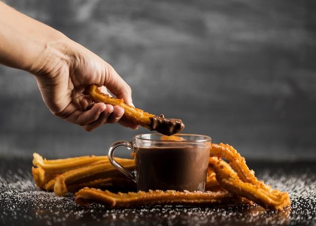 Hand dompelen gebraden churros in chocolade vooraanzicht