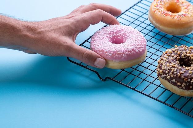 Hand donuts krijgen op blauwe achtergrond.