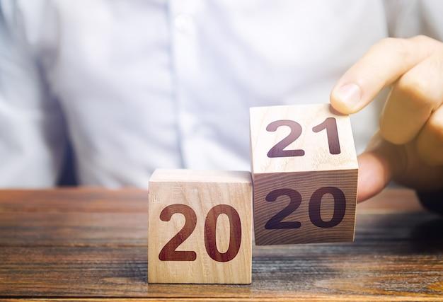 Hand draait een blok om en verandert 2020 in 2021. het nieuwe jaar begint.