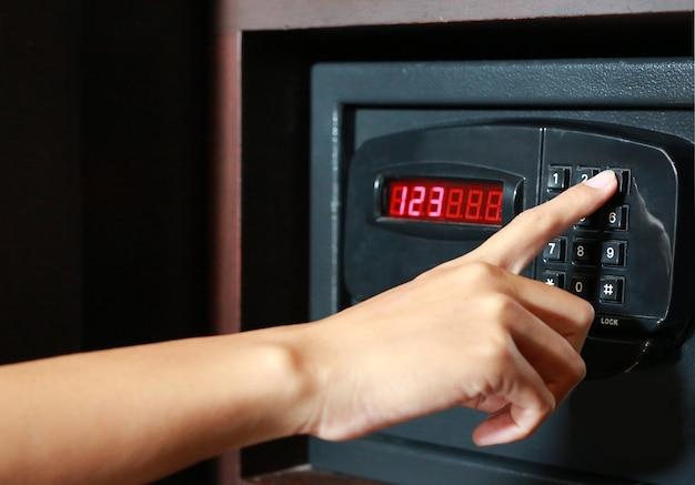 Hand druk op de toets voor vergrendelen of ontgrendelen op zwarte kluis