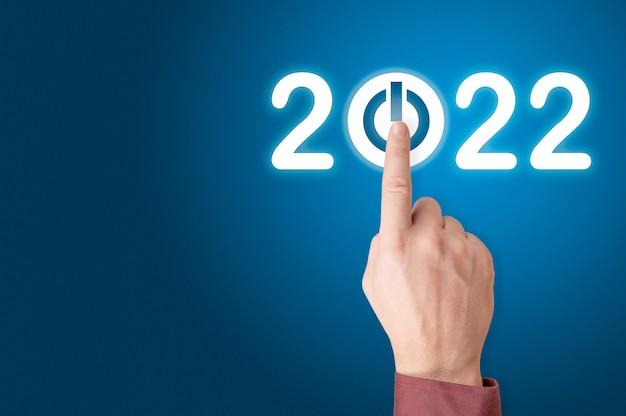 Hand drukt op de startknop voor 2022. vinger op het punt om op de knop te drukken met de tekst 2022 start. jaar tweeduizend tweeëntwintig concept. ruimte kopiëren. blauwe achtergrond