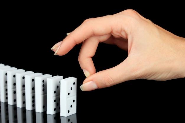 Hand duwen dominostenen geïsoleerd op zwart