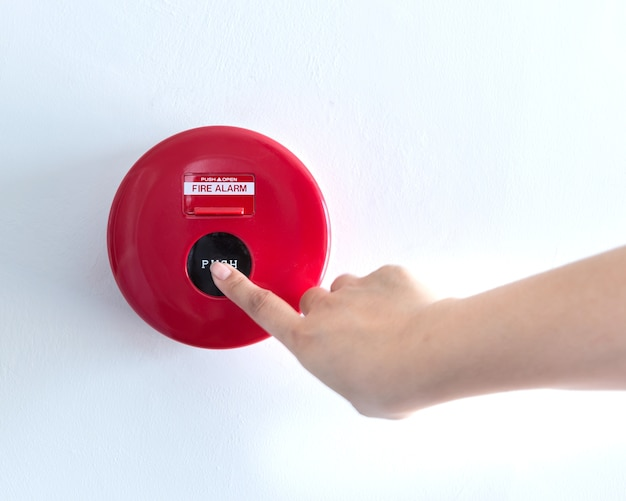 Hand duwt brandalarm schakelaar op de muur