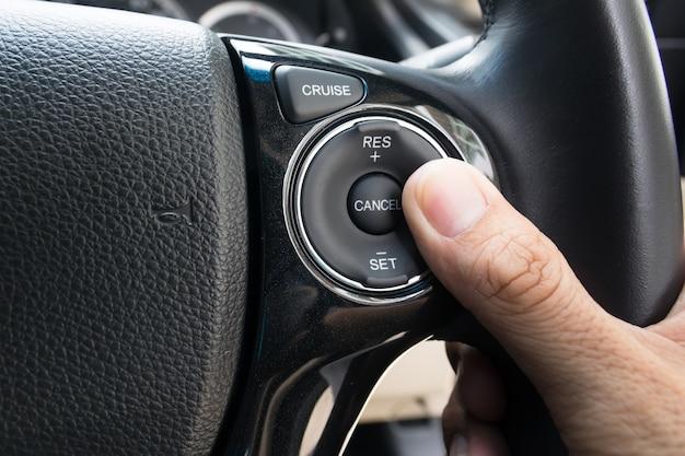 Hand duwt cruise control-knoppen op moderne auto en snelheidsbegrenzing