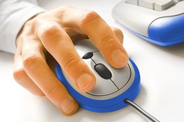 Hand en blauwe computermuis met toetsenbord