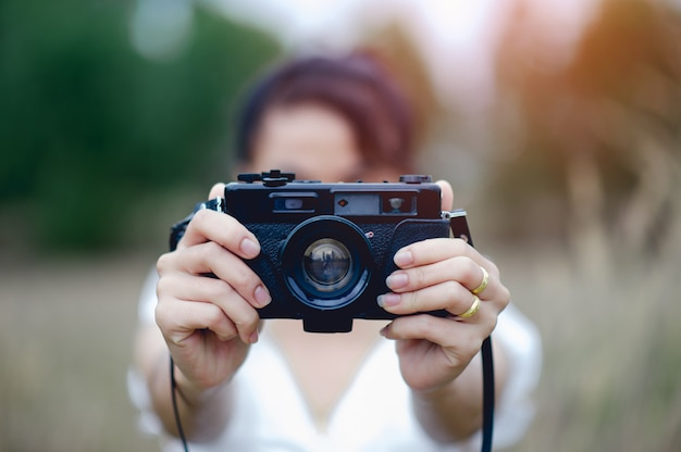 Hand en camera van de fotograaf houden en de camera dragen om foto's te maken