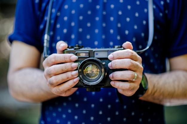 Hand en camera van de fotograaf reis in de bergen en de natuur