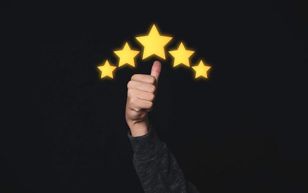 Hand en duim gaan omhoog met gele vijf sterren voor de beste kwaliteit van product en service.
