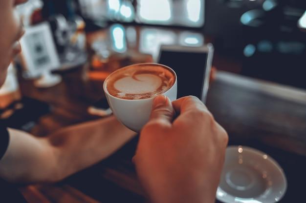 Hand en koffie nemen afstand. drink 's ochtends warme koffie.
