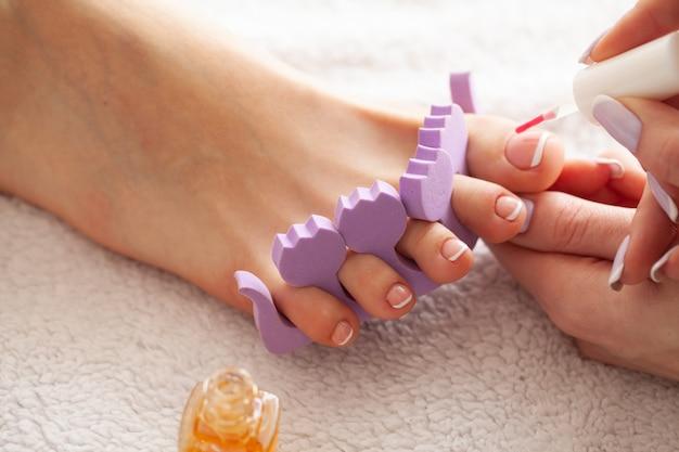 Hand- en nagelverzorging. mooie damesvoeten met pedicure in schoonheidssalon. de meester die nagel toepast. spa manicure