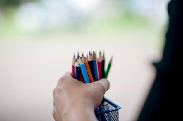 Hand en potlood foto's, groene achtergrondkleur onderwijs concept