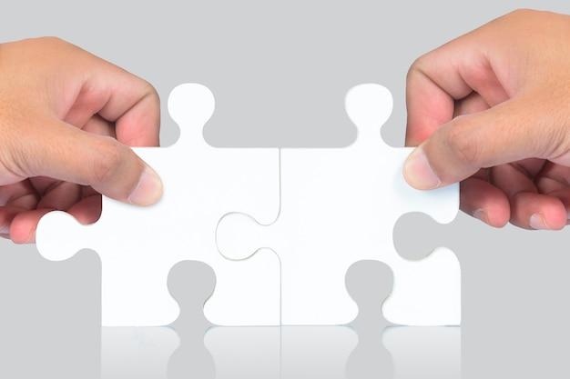 Hand en puzzel stukjes op witte achtergrond
