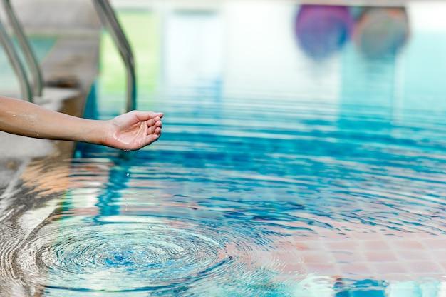 Hand en water raken het blauwe water. het concept verfrissen van schoon water met kopieerruimte opfrissen.