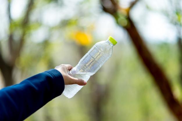 Hand en waterfles drinkwater creatief concept met exemplaarruimte