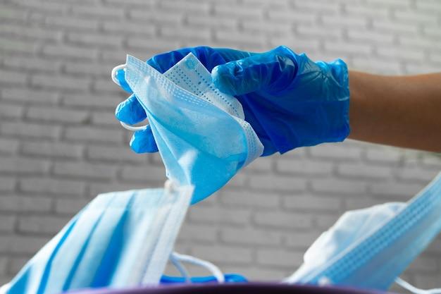 Hand gebruikt vuile chirurgische masker in een vuilnisbak brengen.