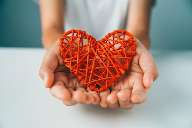 Hand geeft rood hart voor liefde