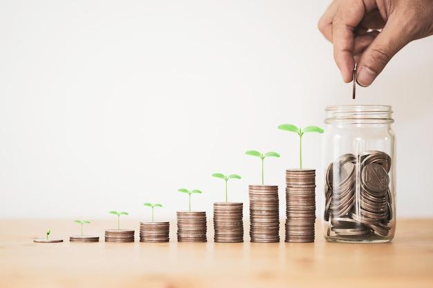 Hand geld munten te sparen doorzichtige pot.