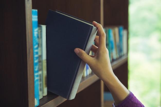 Hand geplukt boeken op boekenplanken in de bibliotheek. onderwijs terug naar schoolconcept