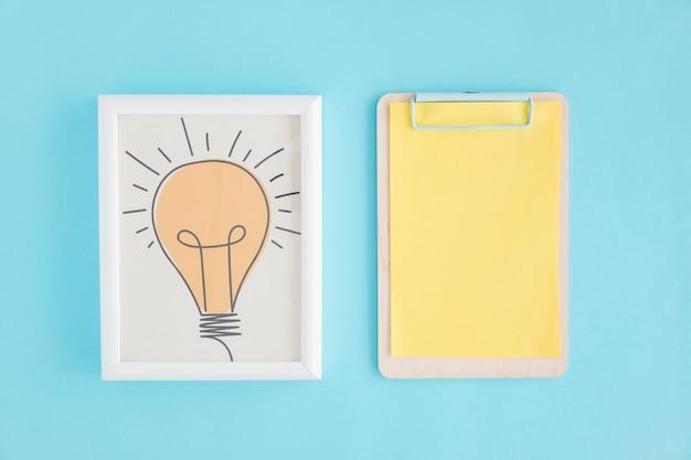 Hand getrokken gloeilamp frame en klembord met geel papier