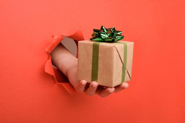 Hand geven geschenkdoos met kraftpapier, door gescheurde rode papieren muur. kopieer ruimte opzij voor uw reclame- en aanbod- of verkoopinhoud.