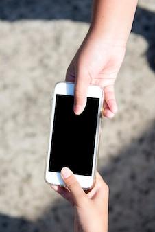 Hand geven van mobiele telefoon met onscherpe achtergrond